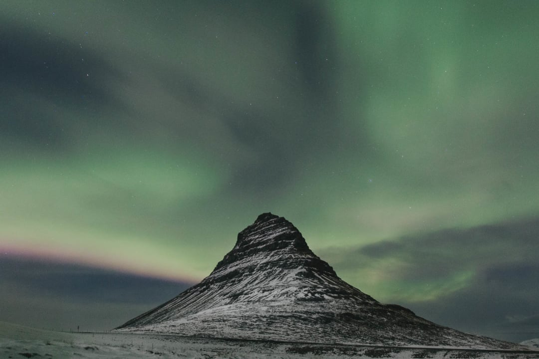 northern lights or aurora borealis at night over Kirkjufell mountain landscape photography of Iceland