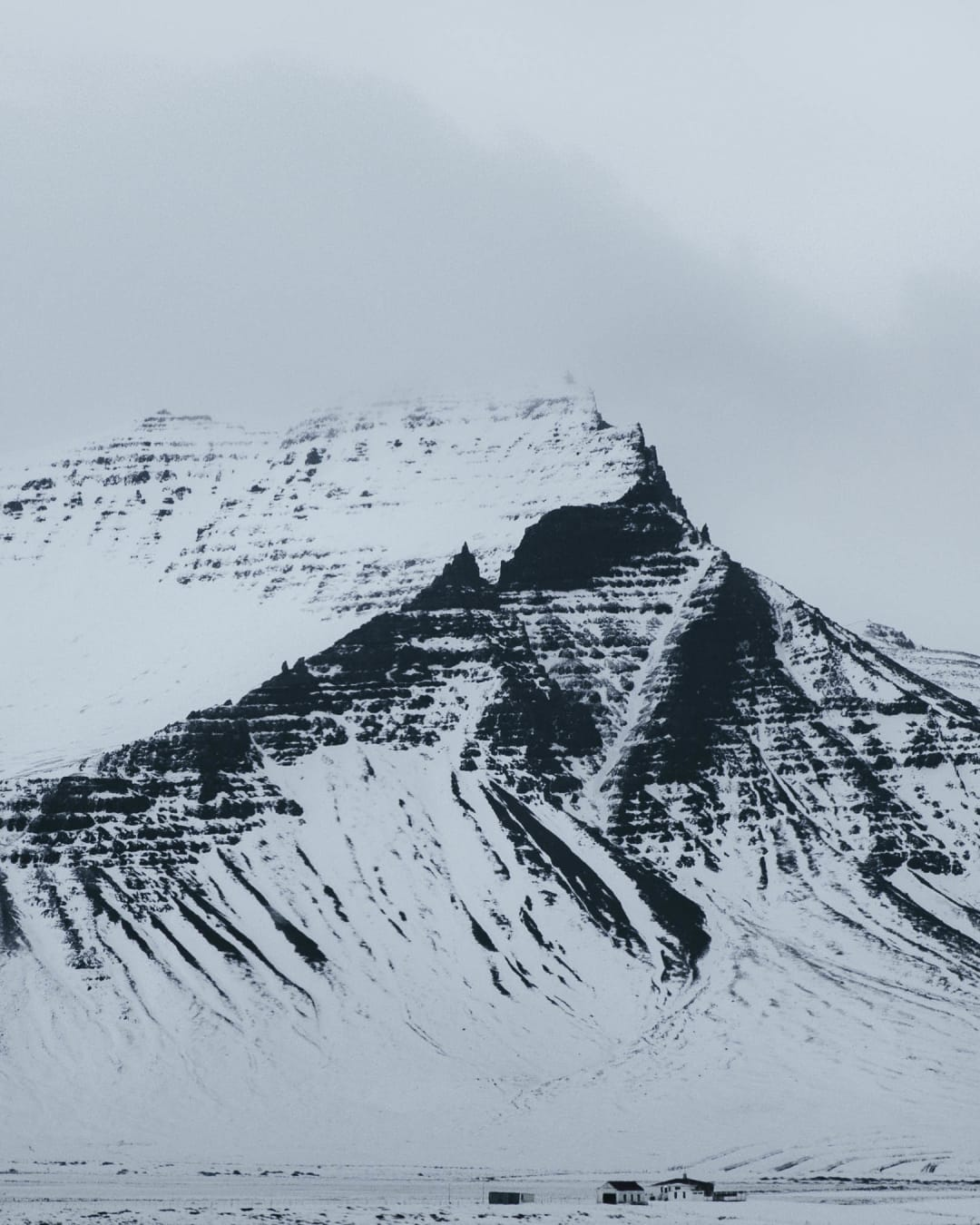 a strong black mountain with white snow on top landscape photography of Iceland