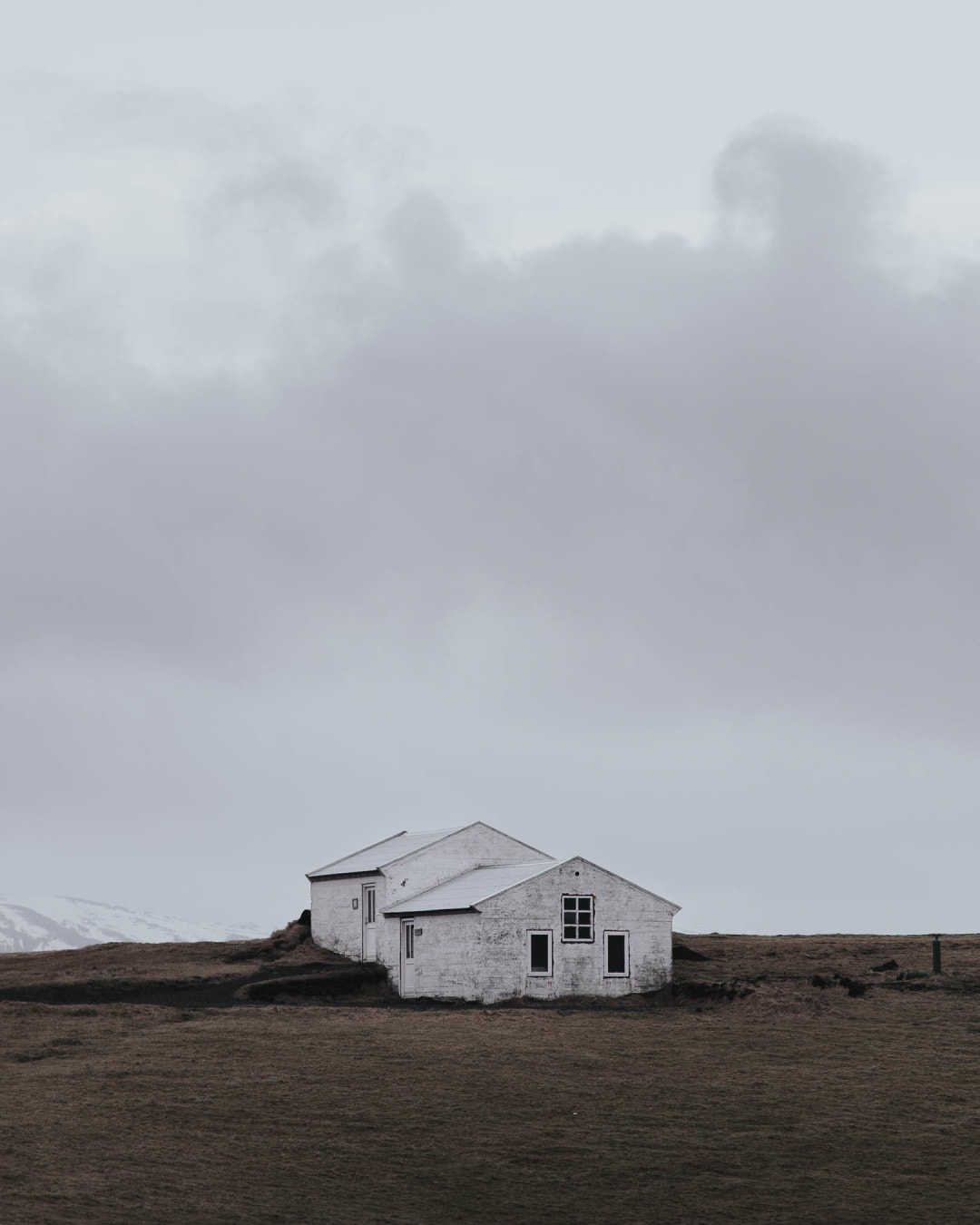 a simple white building and cloudy sky landscape photography of Iceland
