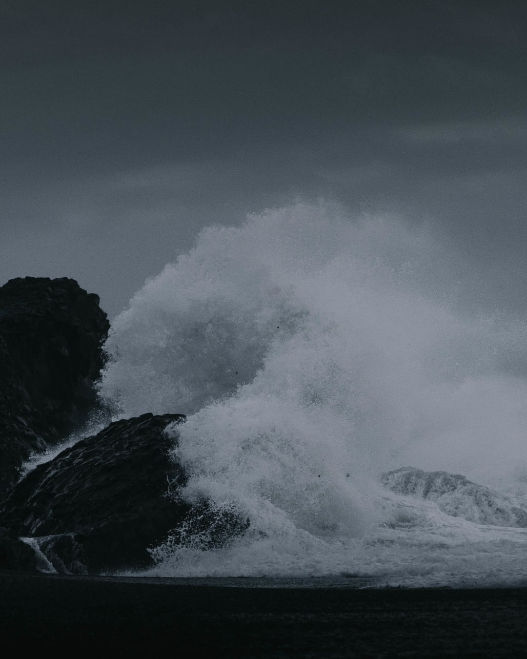 moody waves crashing in to rocks on the beach landscape photography of Iceland
