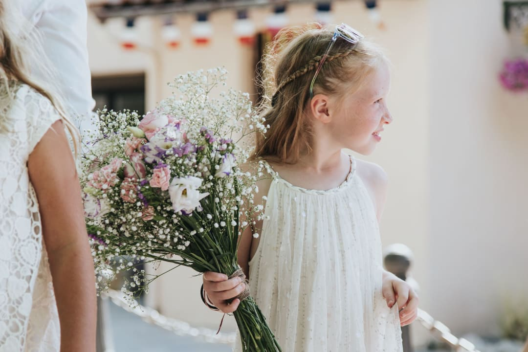 a young girl holding the brides bouquet