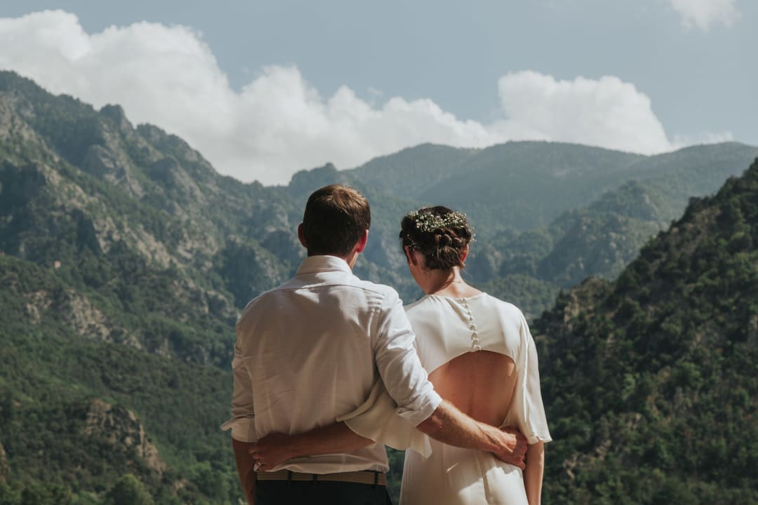 A photograph of the bride and groom looking out into the Pyrenees mountains