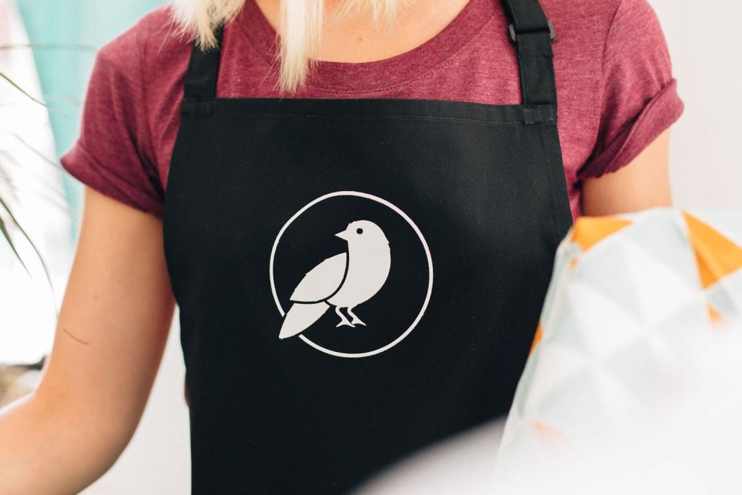 Made By Maria bird logo print onto a black apron