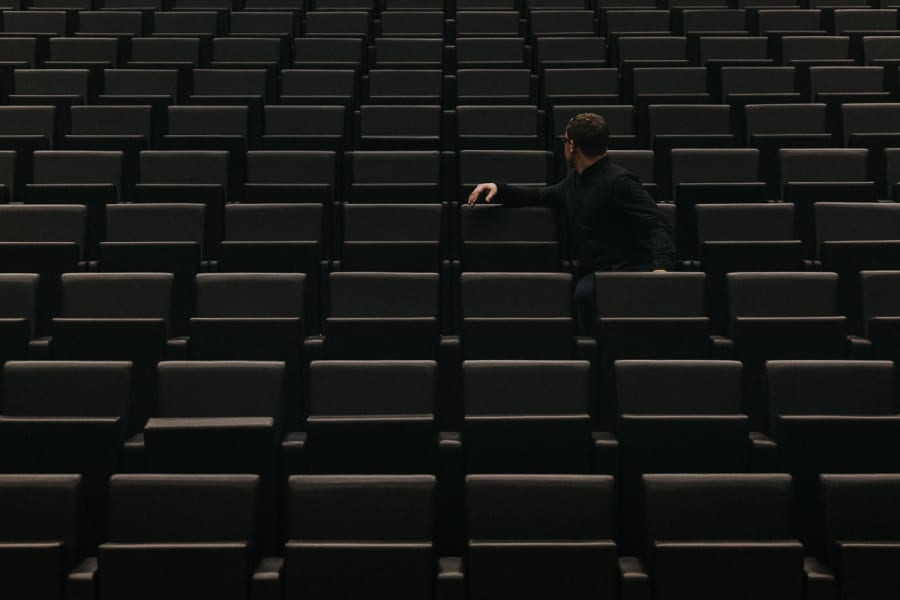 A man sat in an empty theatre room inside the Design Museum