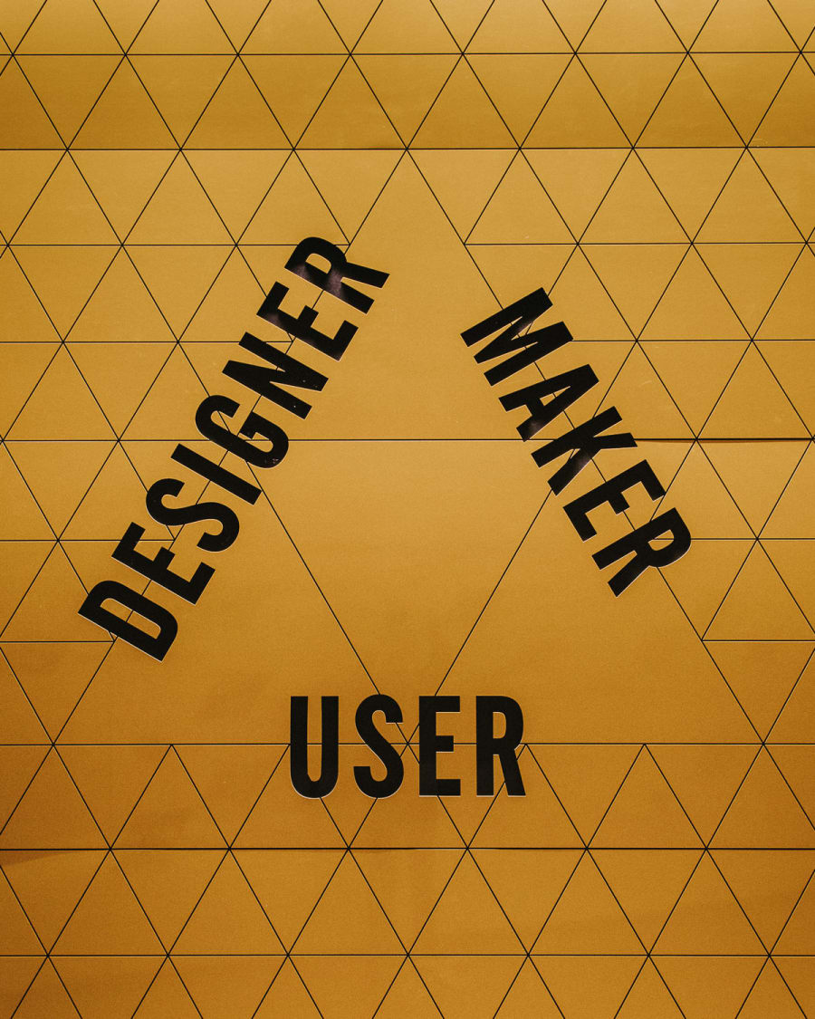 designer, maker, user typography on a yellow tiled wall