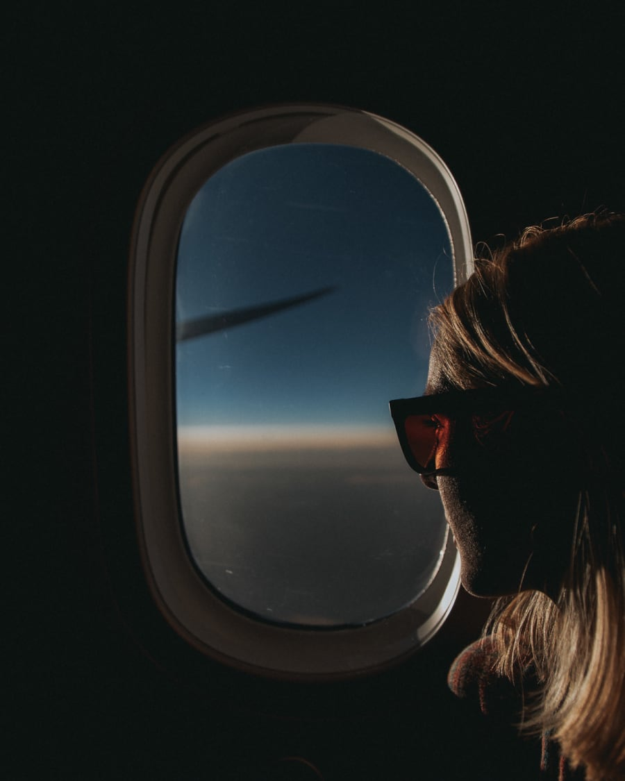 Girl looking out of plane window at sunset wearing Tens sunglasses