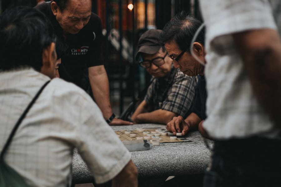 Intimate photograph of men playing and watching a checkers game at The Five Points in Chinatown, Manhattan