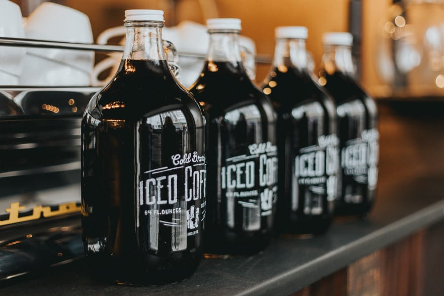 Four large bottles of cold brew iced coffee in a cafe