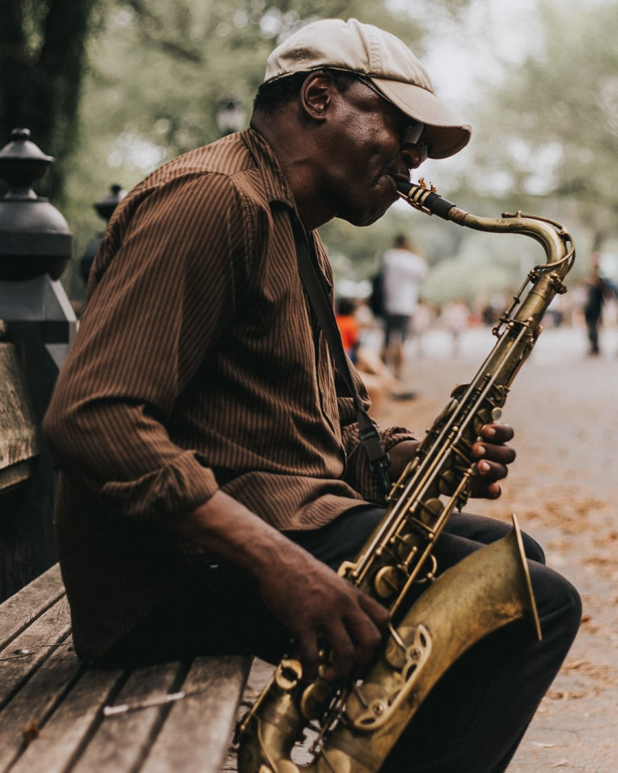 Street performer playing saxophone on a bench in central park
