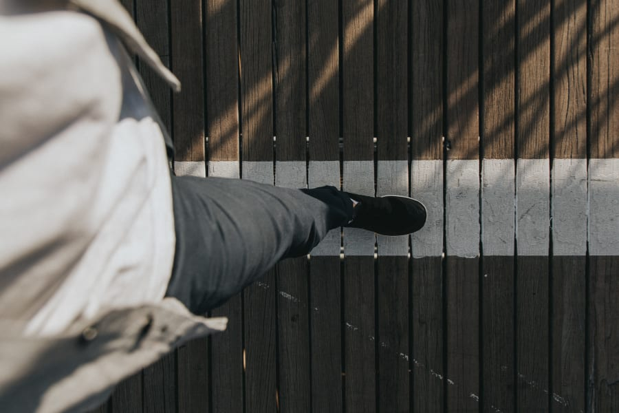 Looking down at feet walking over the wooden beams on Brooklyn Bridge