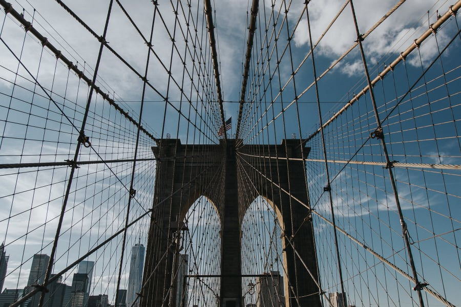 symetrical photo looking up at the arches and wires of Brooklyn Bridge