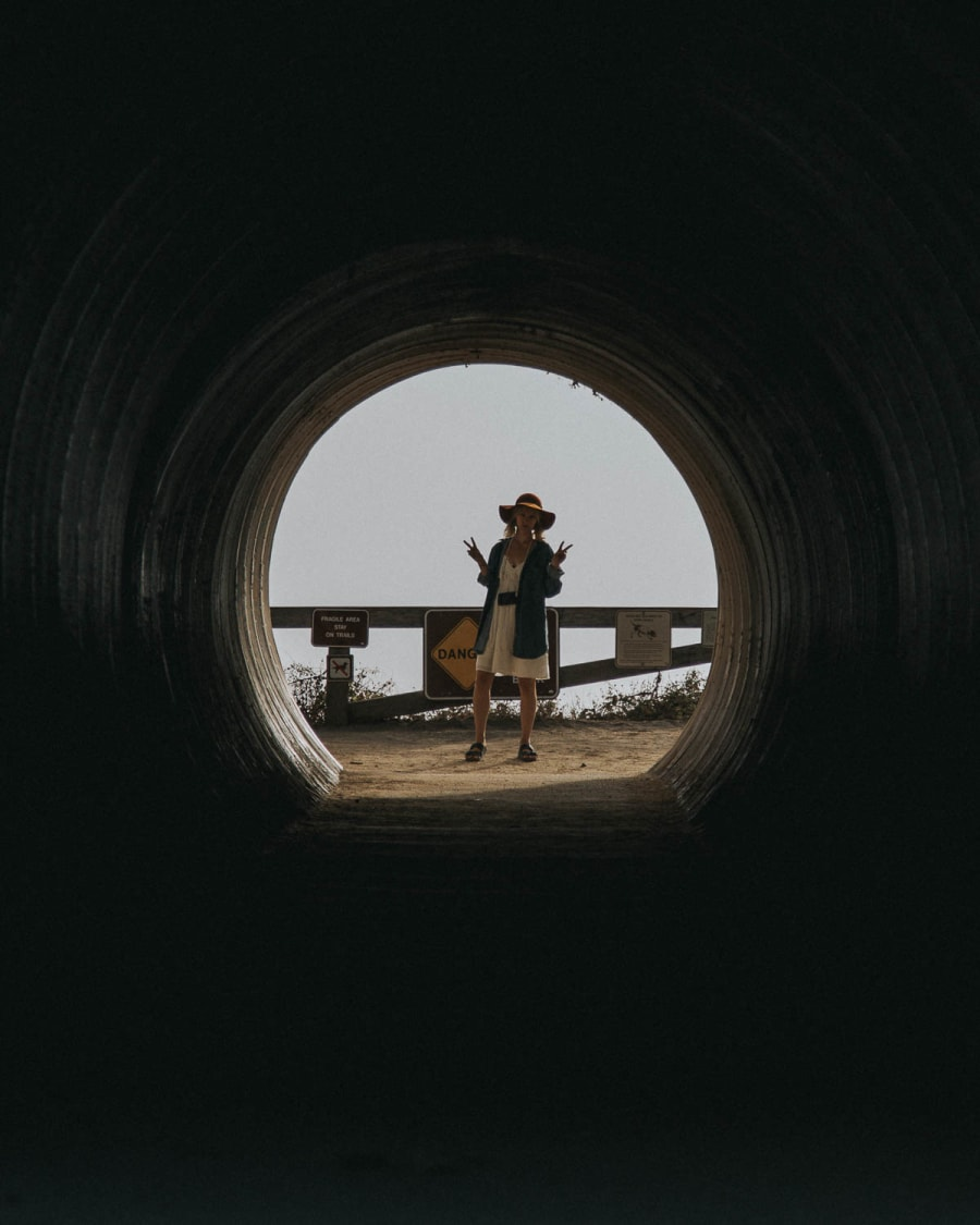 Girl at the end of a tunnel along Cabrillo Highway in California