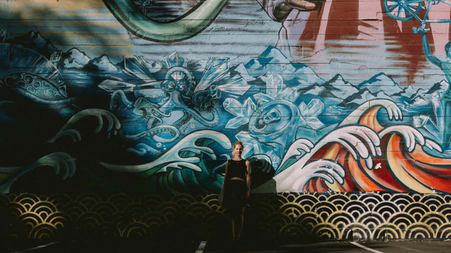 Girl stood in front of a street art mural in Oakland, California