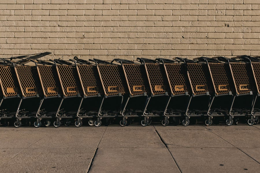 A row of Vons shopping carts against a brick wall