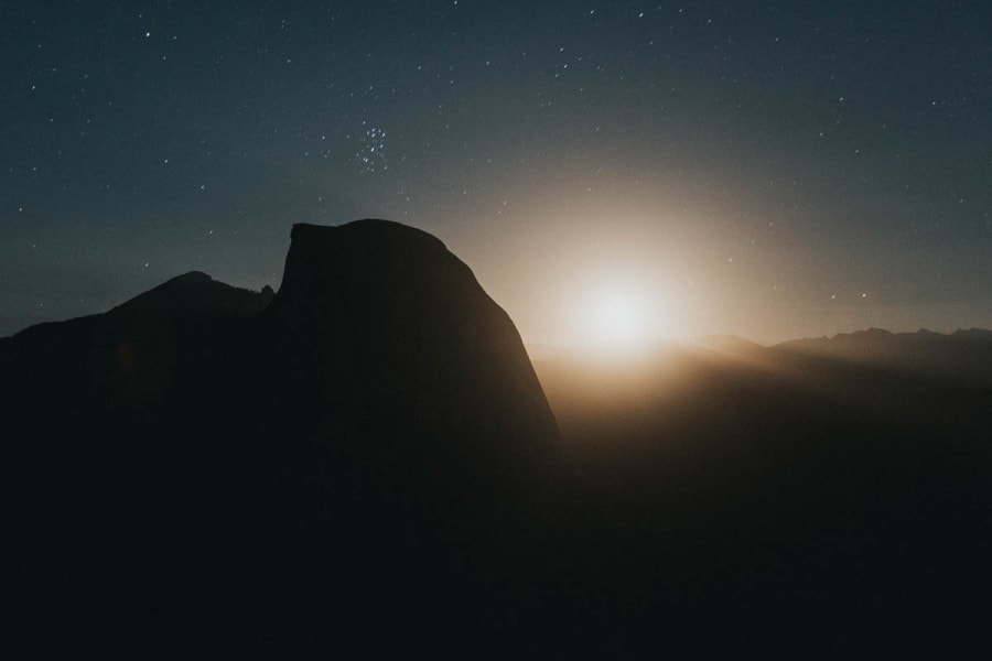 A long exposure of the moon rising behind Half Dome at night. Photographed from Glacier Point in Yosemite National Park