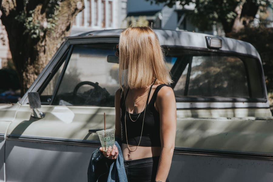 Blonde girl stood in front of a pickup truck on a street in Portland, Oregon.