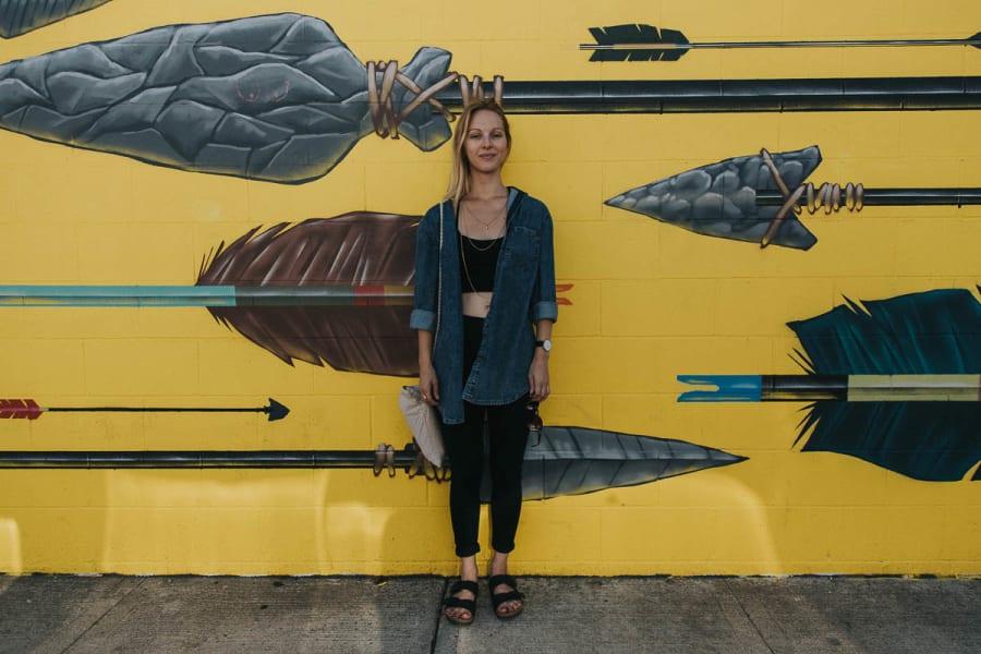 Blonde girl stood in front of a street art mural of arrows in Portland, Oregon.
