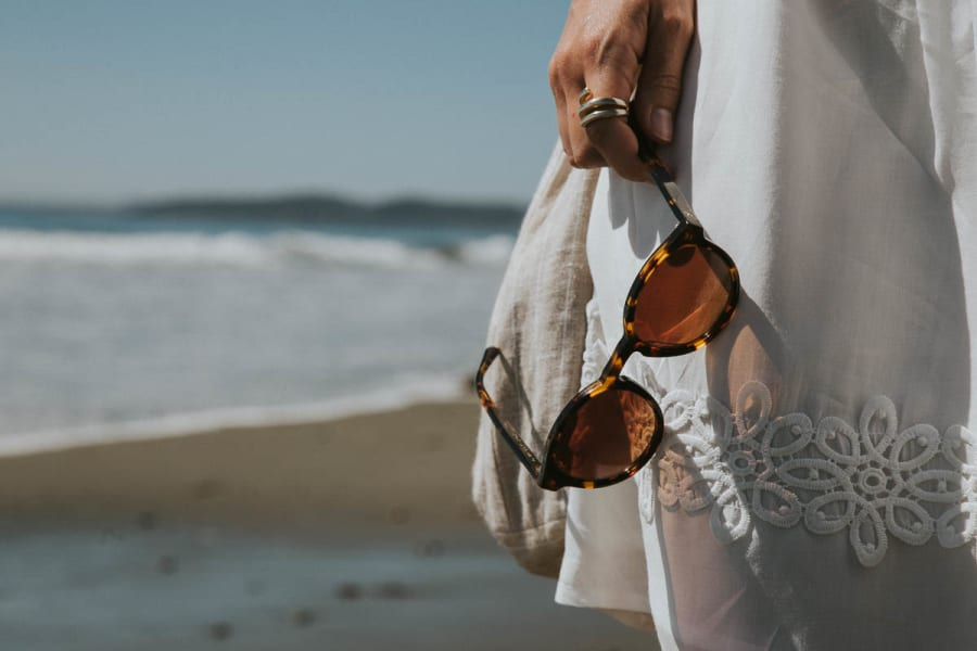Girl in white dress holding Tens sunglasses at the beach