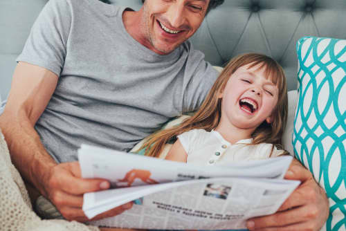 Father daughter reading newspaper