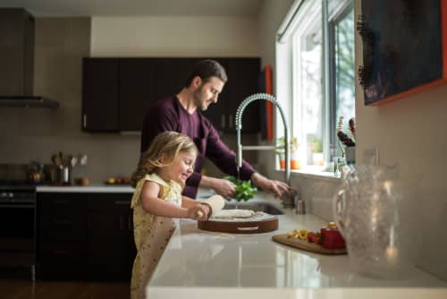 Father rinsing vegetables while daughter rolls out dough