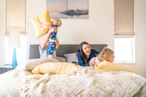 Family playing with pillows in bed