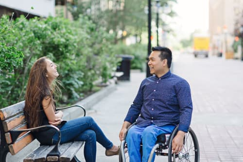 Man in wheelchair talking to daughter on bench