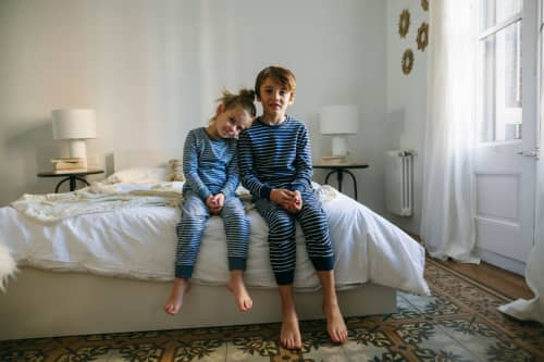 Brother and sister in pajamas waking up