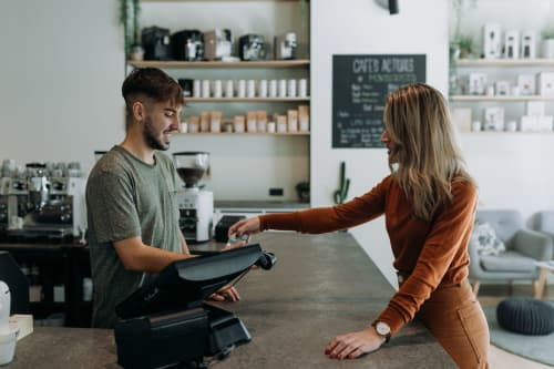 Woman making a purchase from male cashier in coffee shop