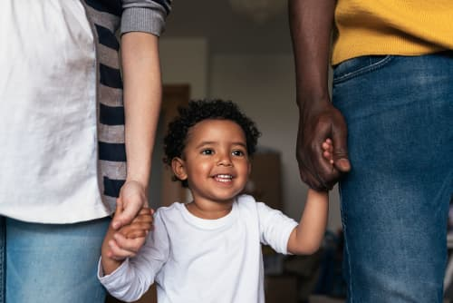 boy-holding-hands-with-parents