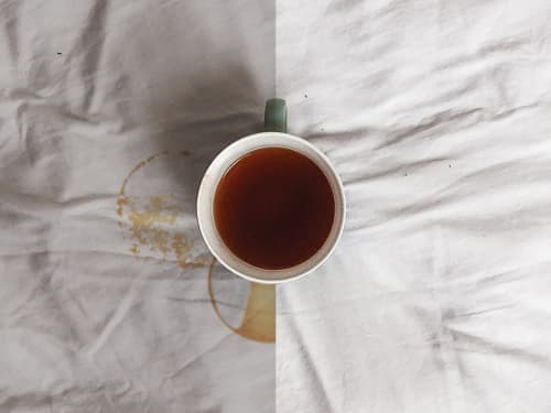 Mug of tea on table with stain