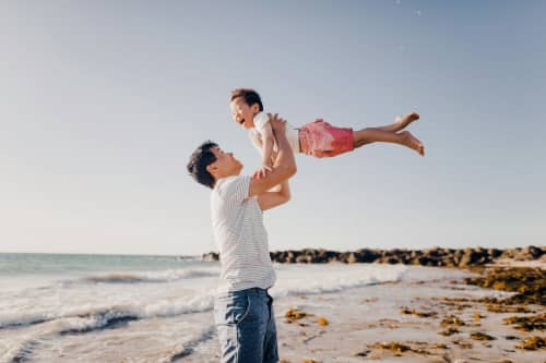 father throwing daughter in the air
