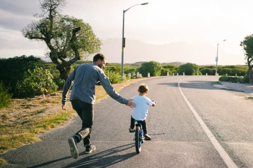 Dad teaching son to ride bike on asphalt road surrounded by trees