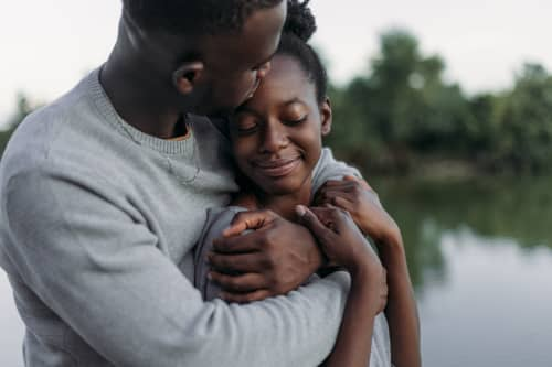 Portrait of a young love couple hugging outdoors at the lake, enjoying