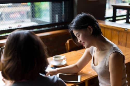 Woman staring at ipad sitting at a table