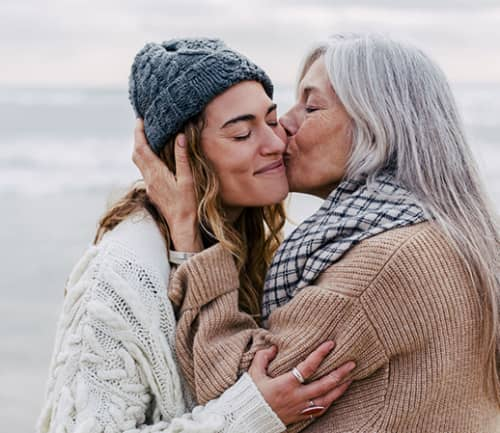 Mother Kissing Her Daughter On The Beach