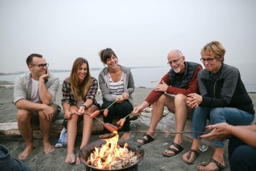 Multigenerational family having a bonfire on the beach
