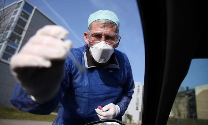 Bác sĩ Đức lấy mẫu xét nghiệm từ một tài xế ở Halle ngày 27/3. Ảnh: AFP.