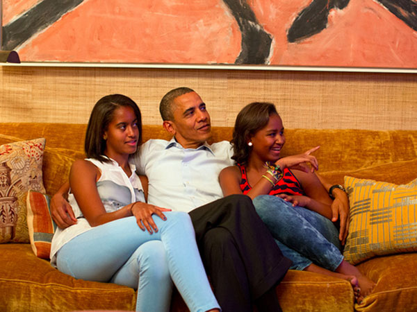 President Obama sitting on a sofa with his daughters