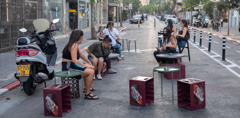 ארגזי בירה משמשים ככיסאות לישיבה ליד בתי קפה ברחוב לוינסקי בתל אביב / צילום: כדיה לוי