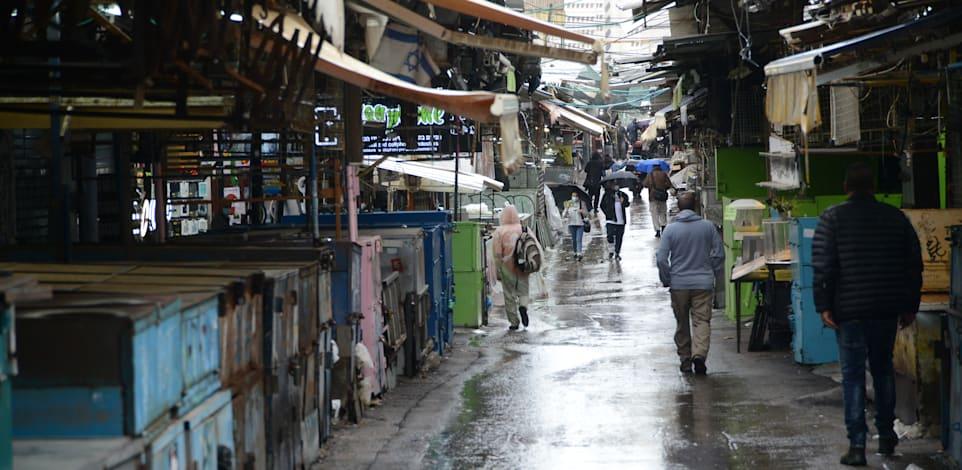 """שוק הכרמל ת""""א - חנויות פתוחות לצד בסטות סגורות / צילום: איל יצהר"""