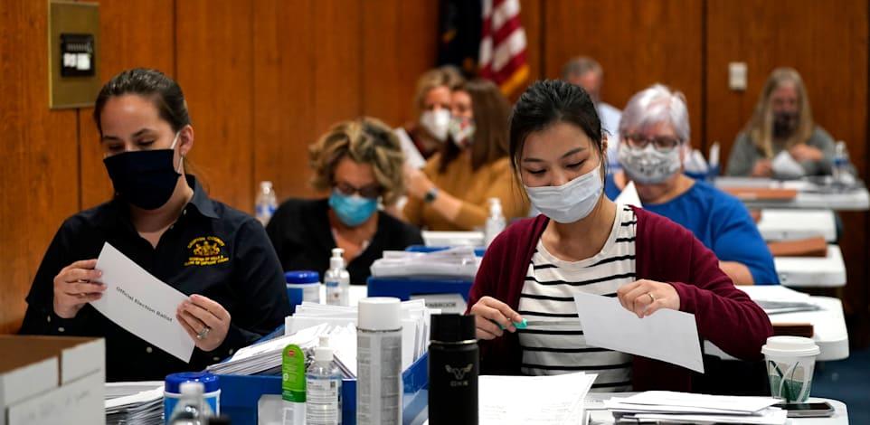 """עובדים בקלפי סופרים הצבעות שנעשו דרך הדואר בבחירות בארה""""ב / צילום: Associated Press, Julio Cortez"""