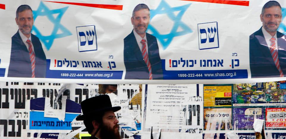 """הבטחה של """"פנסיה לכל עובד"""" בשלטי תעמולה בירושלים בבחירות 2009 / צילום: Reuters, Yannis Behrakis"""