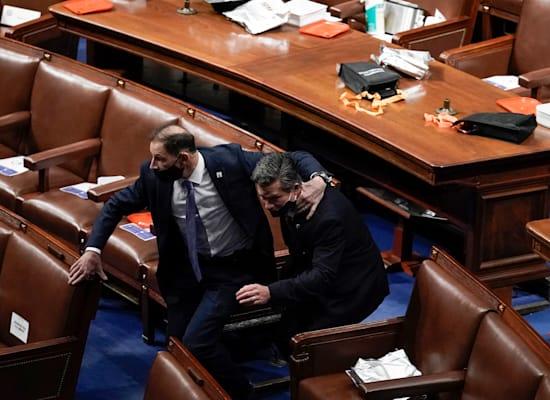 אנשי ביטחון מוציאים את המחוקקים מתוך אולם הקונגרס בעוד המפגינים מסתובבים בתוך גבעת הקיפטול / צילום: Associated Press, J. Scott Applewhite)