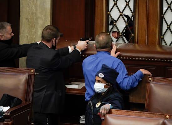 שוטרים ואנשי ביטחון עם אקדחים שלופים מול מפגינים שמאיימים לפרוץ לתוך חדרי הקפיטול / צילום: Associated Press, J. Scott Applewhite
