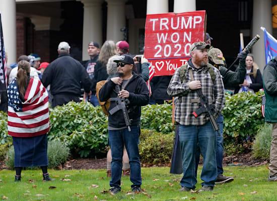 תומכי טראמפ נושאי נשקים מחוץ לבית המושל לאחר שפרצו את הגדרות המקיפות / צילום: Associated Press, Ted S. Warren
