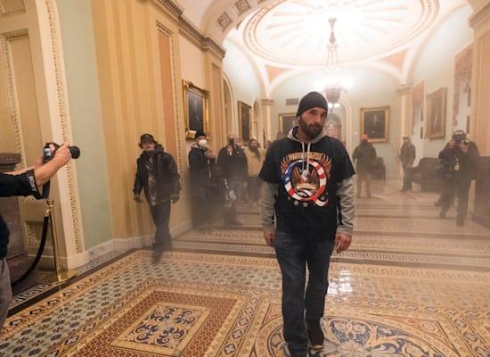 מפגין תומך-טראמפ עם חולצה של Qanon צועד בין רימוני עשן בתוך גבעת הקפיטול / צילום: Associated Press, Manuel Balce Ceneta
