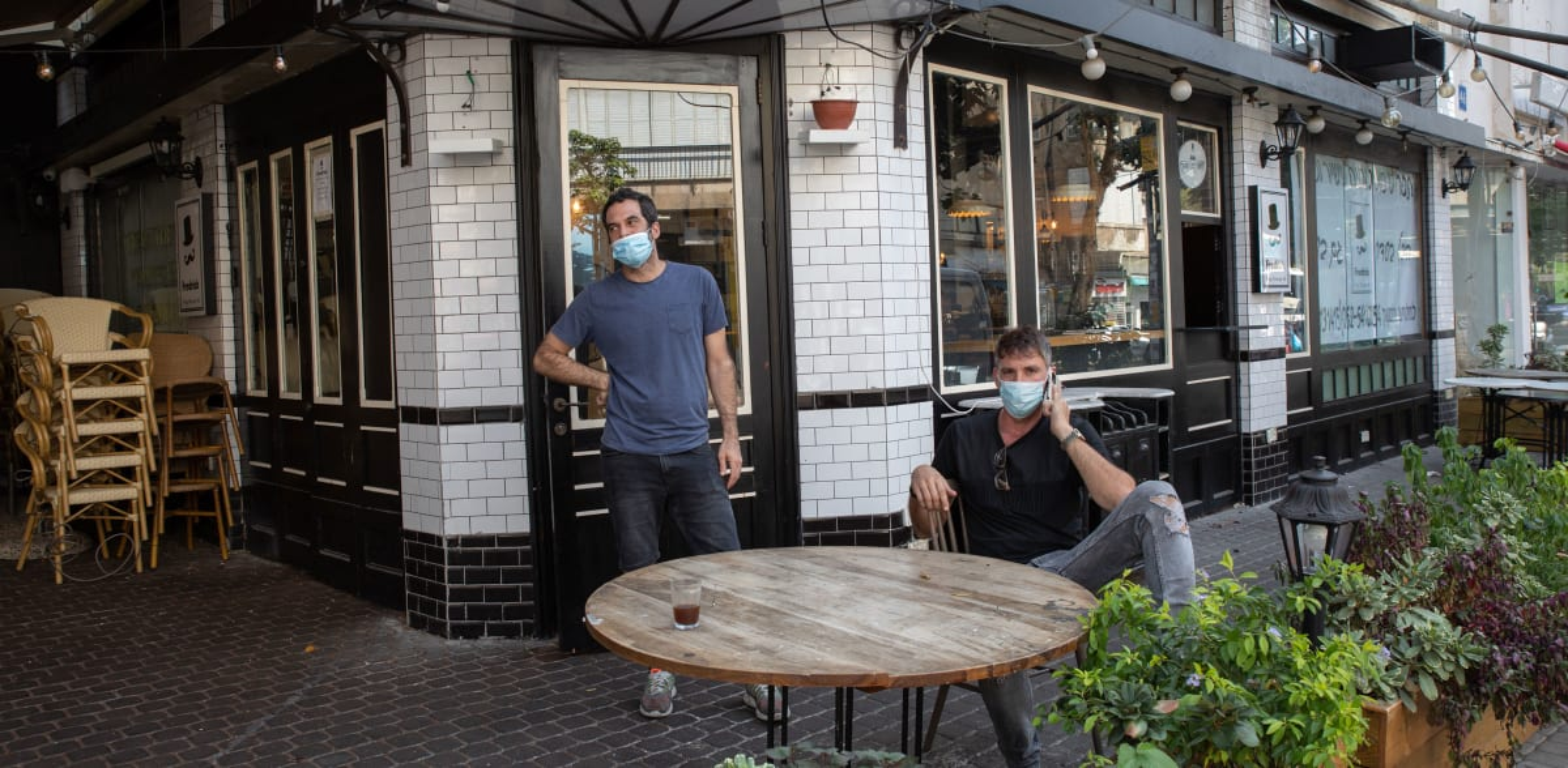 בעלי עסקים יושבים מחוץ לעסקיהם הסגורים. המשק רחוק מחזרה לשגרה / צילום: כדיה לוי
