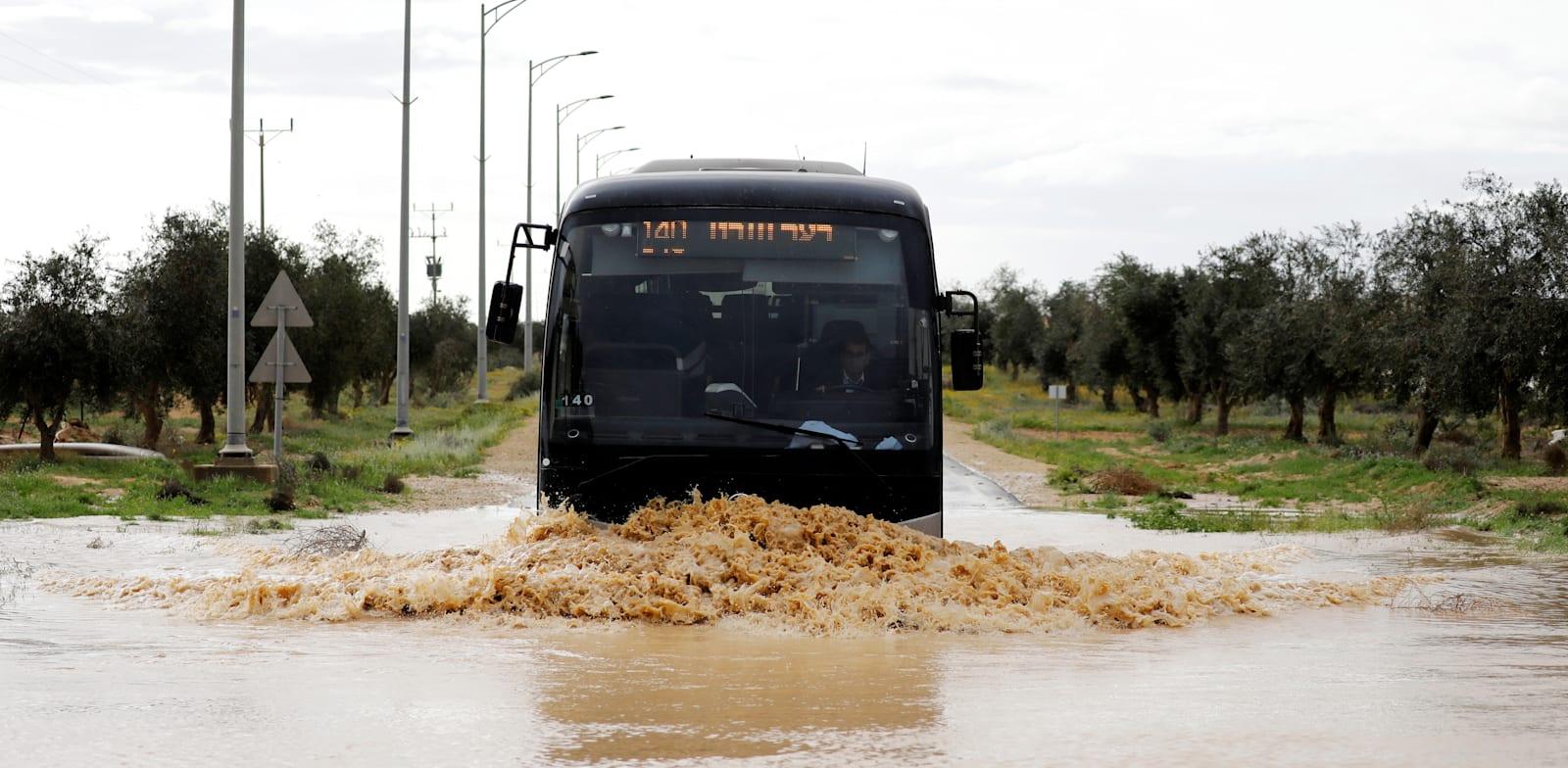 אוטובוס חוצה כביש מוצף ליד באר מילכה. ההצעה היא להקים אתרי ויסות / צילום: Reuters, Amir Cohen