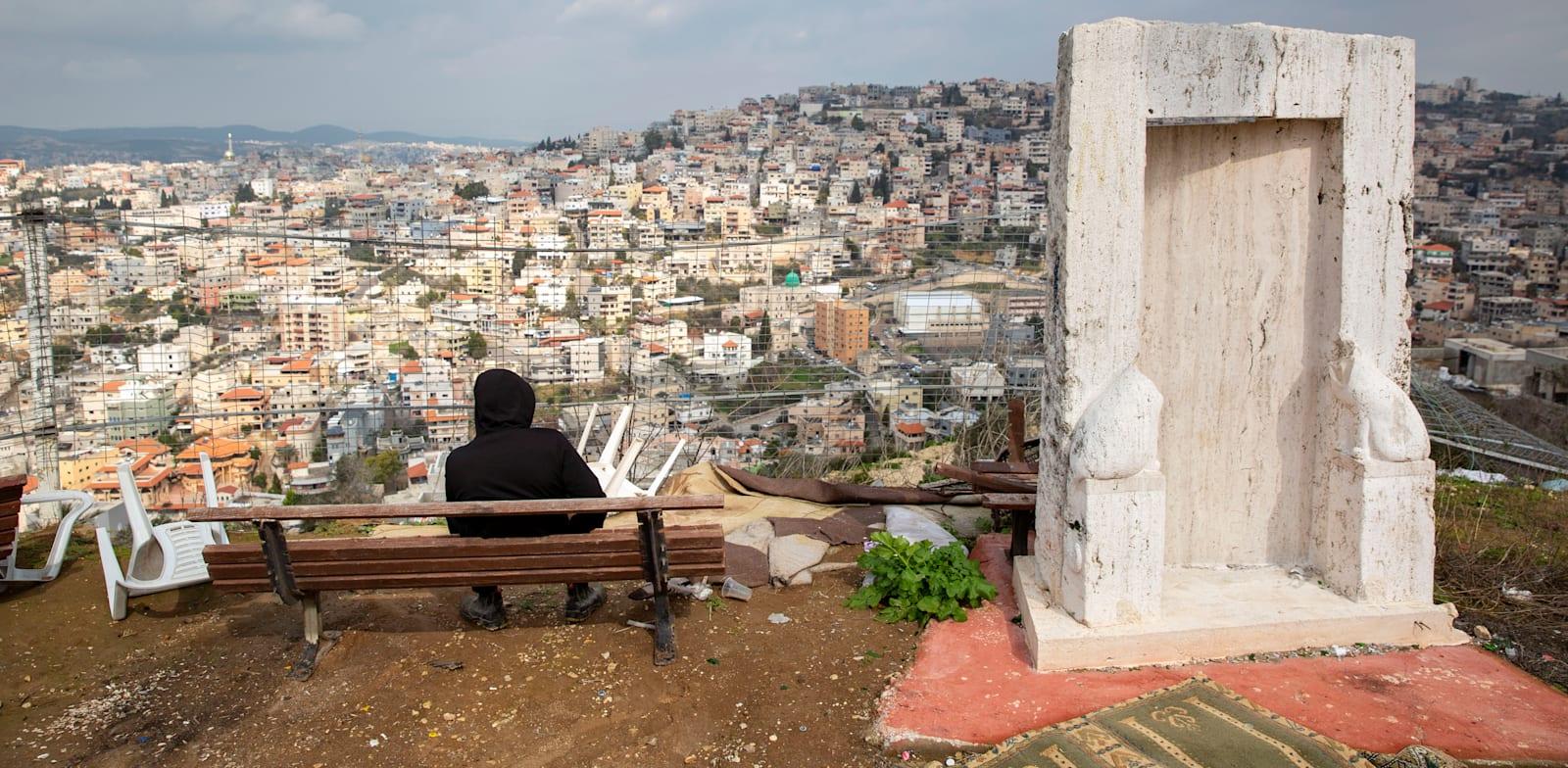 צעיר צופה על העיר אום אל פאחם / צילום: Associated Press, Oded Balilty
