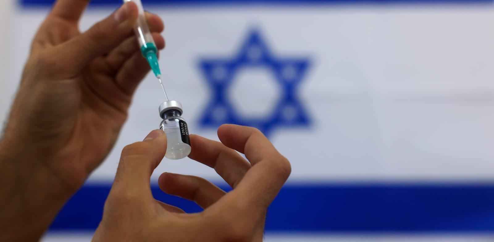 פרמדיק צבאי מכין חיסון קורונה להזרקה באשדוד / צילום: Associated Press, Tsafrir Abayov